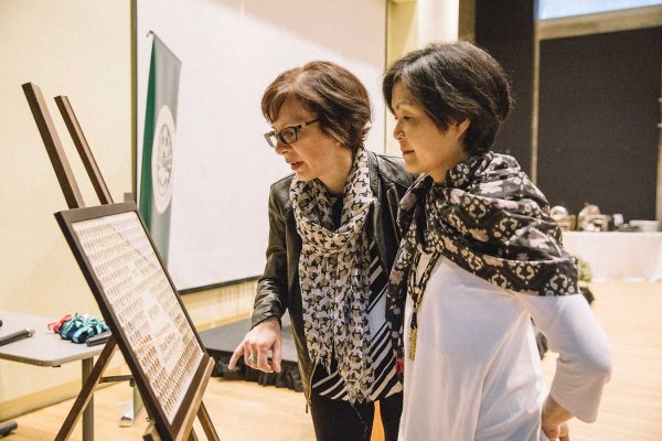Two women looking at the 1992 graduating class composite in New College's William Doo Auditorium.