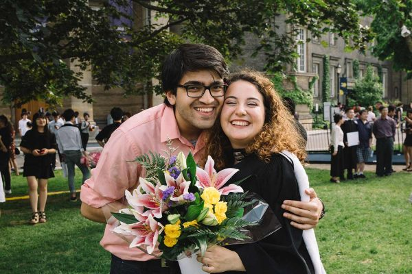 Female graduate with a male friend and flowers.