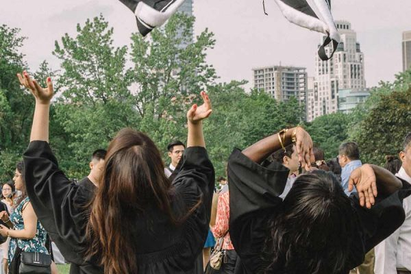 Robed New College students trowing their bachelor's hoods into the air.