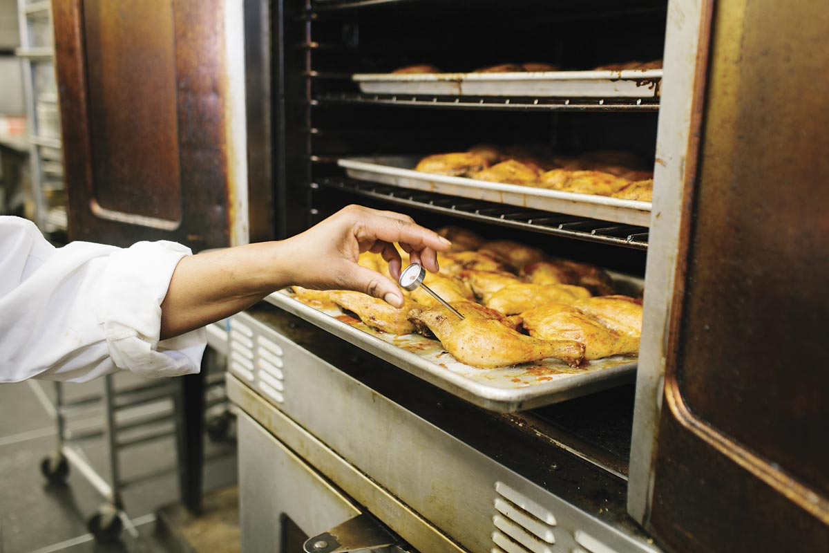 A hand checking the temperature of cooed chicken in an oven.