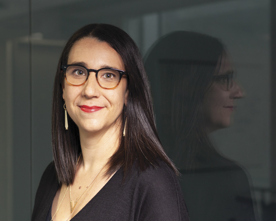 Portrait of a woman with long, dark hair and glasses, smiling at the camera [Anne McGuire].