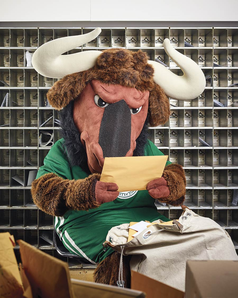 Portrait of the New College mascot Goliath Gnu (a wildebeest dressed in a green New College jersey) sitting and reading a letter, with a large bag of letters by his feet and a wall of mail slots behind him.