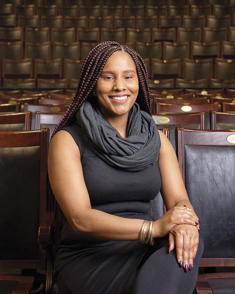 Portrait of a seated, smiling woman with box braids and folded hands [Lydia Gill in U of T's Convocation Hall]; rows of seats visible behind her.