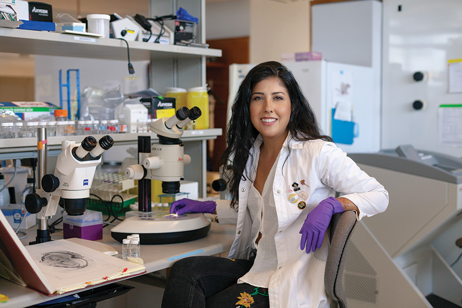 Portrait of a scientist with long dark hair [Samantha Yammine] in a lab coat next to microscopes and an open brain atlas.